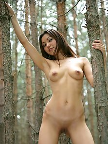Sweet Asian beauty showing her naked body in a dark forest