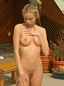 Blonde strips nude and spreads pussy lips to catch some sun on her pink stuff