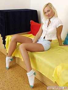 Blonde babe in white socks puts a purple dildo into her vagina