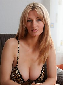 Busty blonde babe gets naked on the couch