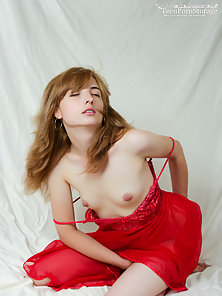 Pretty girl poses in a sexy red lingerie and strips nude to play with her tight pink pussy.