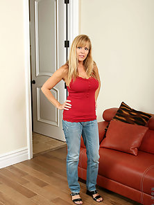 Enticing mature babe flaunts her sexy cougar body in jeans and a red tank top