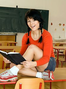 Busty schoolgirl showing her sexy curved body in classroom