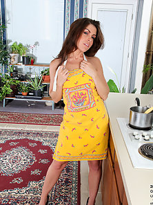 Sexy soccer mom wears just a thong and apron as she cooks in the kitchen