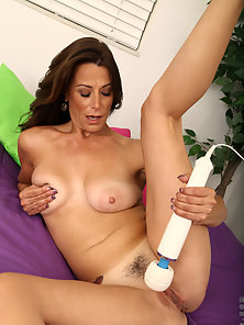 Mature woman caresses her milf pussy with the magic wand