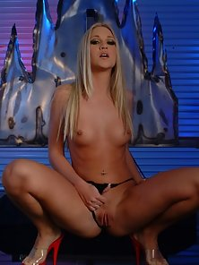 Blonde pornbabe posing seductively in dimly lit room