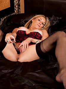 Horny housewife in lingerie masturbates with a dildo in bed while hubby is away