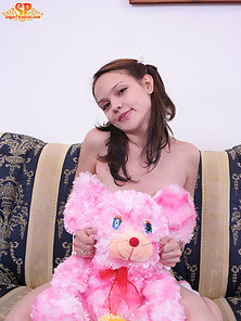 Lovely teen girl seats on the sofa with her pink teddy bear, then she undresses and demonstrates her