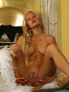 Blond babe plays with feather boa