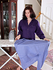 Sexy housewife Kinsey unbuttons her blouse revealing cleavage while ironing