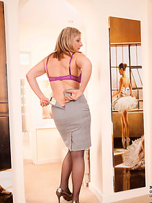 Office exec slips off her business suit revealing her sexy bra and panties