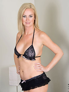 Hot Anilos woman strips off her black bra on the sofa and spreads her long legs