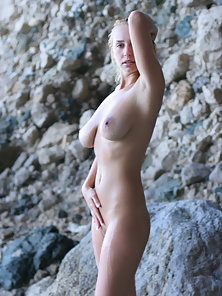 Wet blond russian shows off her big natural boobs in a rocky cavern.