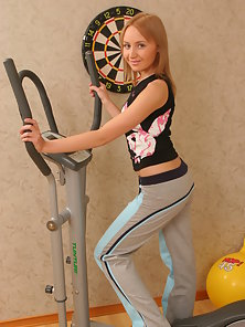 Playful sporty chick is posing her beautiful body right in the gym room.