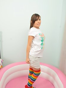 Adorable brunette teen in stripped stockings plays with whipped cream and a pink toy