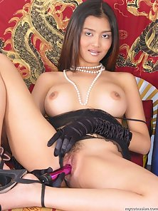 Busty Thai babe in black lingerie inserts a dildo in her asian pussy