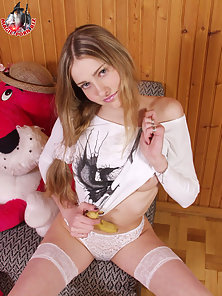 Sexy teen in white stockings playing with a banana and taking off her shirt