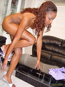 Gorgeous ebony babe strips clothes in couch
