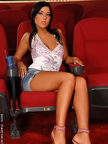 Brunette babe stripping and masturbating in cinema