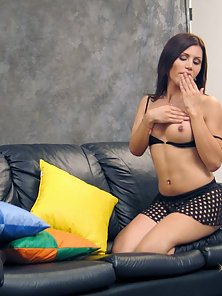 A sexy shemale gets naked on a leather couch
